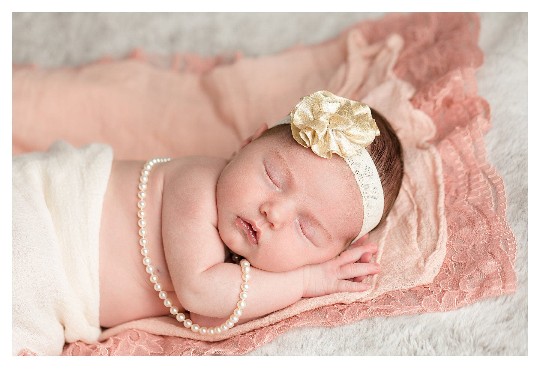 newborn on pink and gray with pearls